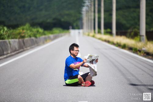 道路で新聞を読む男性